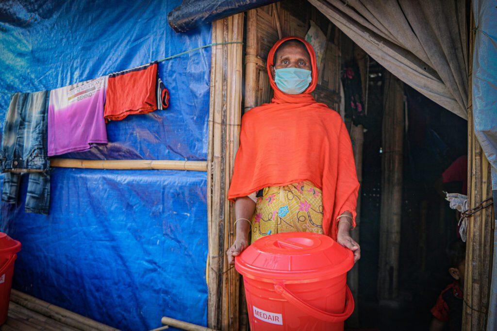 Vrouw houdt haar ontvangen pakket vast op de drempel van haar onderkomen.